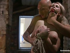 This sexy blonde babe, Isabella Clark, gets abducted by a bald stud and taken to a quiet place. Her mouth is ball gagged and this babe is completely naked! The stud tied her on a bed and left her there. After a while, a stud comes in and starts teasing her with his cock and fucks her from behind