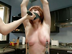 Odille has a strap on dildo attached on her face and with her hands bound and clamps on her nipps and cookie that playgirl waits patiently in the kitchen for the blonde milf to undress. After the blonde is naked, with a little aid and guidance that playgirl insets the dildo in that shaved cunt, fucking it like a submissive slut.